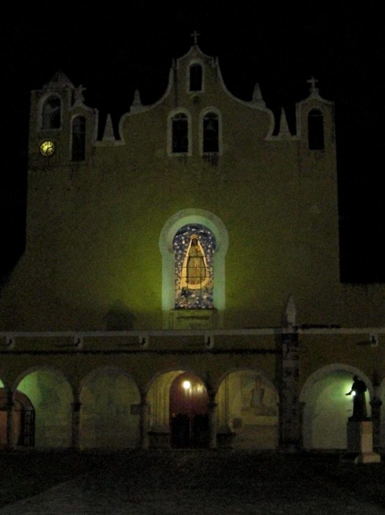 P'ap'hol Chaak - Front der Klosterkirche mit Glasfenster bei Nacht - die Figur vorne rechts stellt Diego di Landa dar